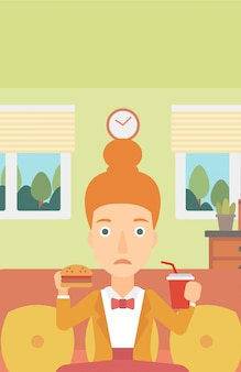 Donna che mangia hamburger.
