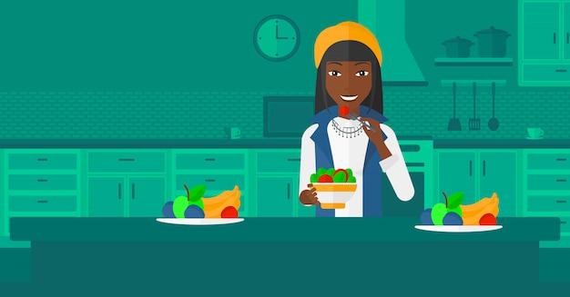 Donna che mangia insalata.