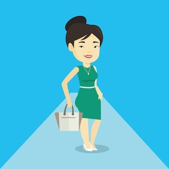 Donna che posa sulla passerella durante la sfilata di moda.