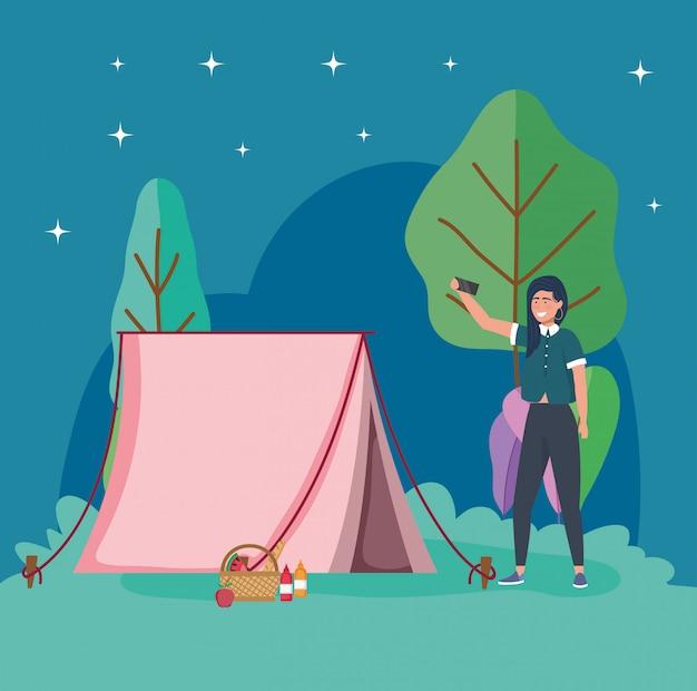 Donna che prende il picnic di campeggio della tenda di notte del selfie