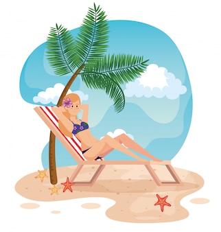 Donna che prende il sole nella sedia d'abbronzatura con la palma