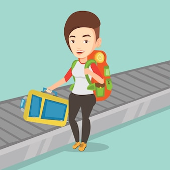 Donna che prende valigia sul nastro trasportatore dei bagagli