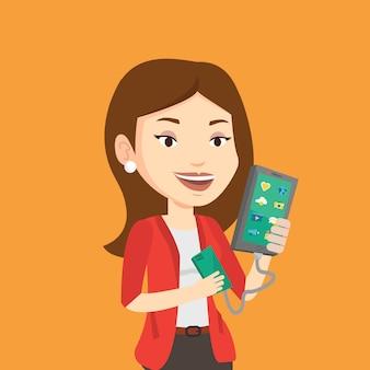 Donna che ricarica smartphone dalla batteria portatile.
