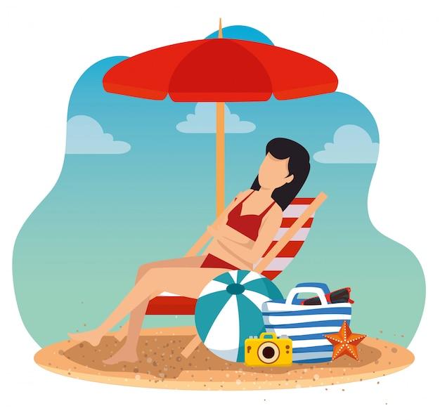 Donna che si distende nella sedia abbronzante con ombrello e borsa