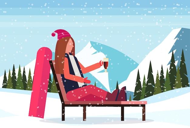 Donna che si rilassa sulla sedia di salotto dopo lo snowboard alla stazione sciistica