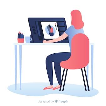 Donna che si siede al posto di lavoro del progettista grafico