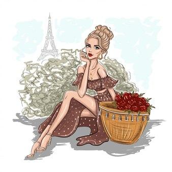 Donna che si siede con la borsa di paglia e fiori