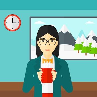 Donna che si siede con la tazza di caffè