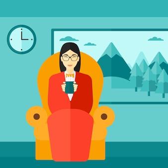 Donna che si siede nella sedia con la tazza di tè