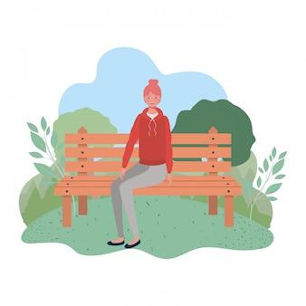 Donna che si siede nella sedia del parco con il paesaggio