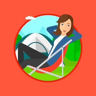 Donna che si siede nella sedia pieghevole nel campo.