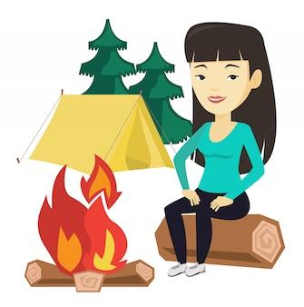 Donna che si siede sul ceppo vicino al fuoco di accampamento nel campeggio.