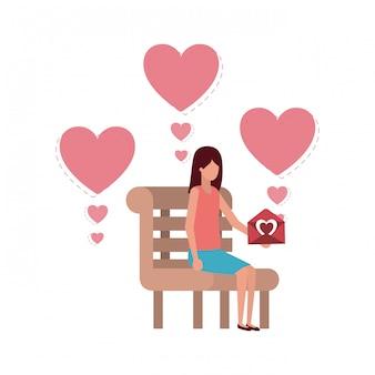 Donna che si siede sulla sedia del parco con carattere di cuori