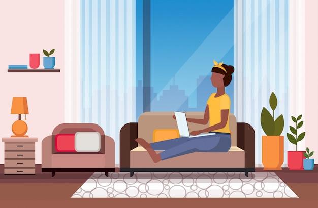 Donna che si siede sullo strato facendo uso dell'orizzontale integrale interno interno del salone moderno di concetto di dipendenza digitale di comunicazione della rete di media del computer portatile
