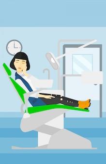 Donna che soffre nella poltrona del dentista.