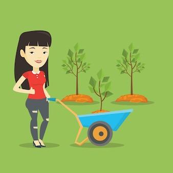 Donna che spinge carriola con la pianta.