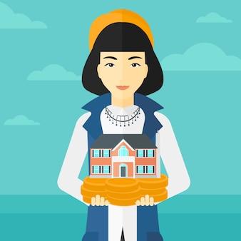 Donna che tiene il modello di casa.