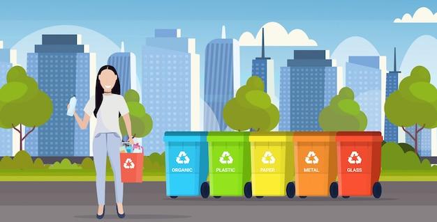 Donna che tiene il secchio con rifiuti di plastica vicino a contenitori diversi tipi di contenitori per il riciclaggio segregare la raccolta differenziata concetto moderno paesaggio urbano sfondo piatto orizzontale a figura intera