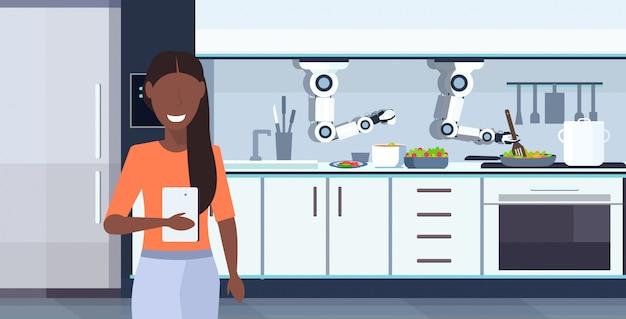 Donna che usando app mobile che controlla il robot pratico astuto del cuoco unico che prepara il ritratto orizzontale interno della cucina moderna di concetto di intelligenza artificiale dell'innovazione dell'assistente robot dell'omelette delle uova fritte e