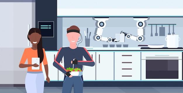 Donna che utilizza app mobile uomo di controllo umanoide con fili elettrodi indicatori a portata di mano robot chef utile preparare cibo robot assistente concetto moderno cucina interno orizzontale ritratto