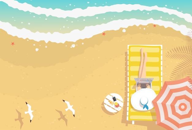 Donna con cappello da spiaggia e laptop sul sole