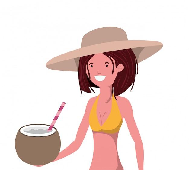 Donna con costume da bagno e acqua di cocco in mano