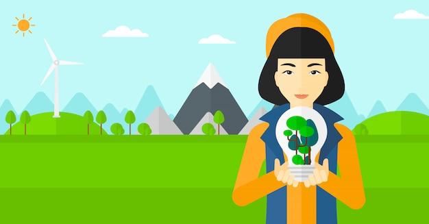 Donna con la lampadina e gli alberi dentro