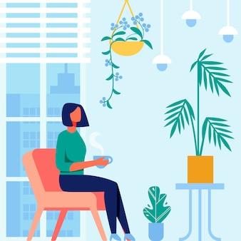 Donna con la tazza di tè in camera con interni blu
