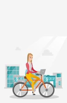 Donna d'affari in sella a una bicicletta con un computer portatile.