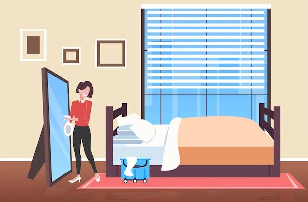 Donna detergente tenendo straccio e spray bottiglia di plastica bidello femmina spray e pulendo specchio servizio di pulizia concetto moderno camera da letto interno a figura intera schizzo orizzontale