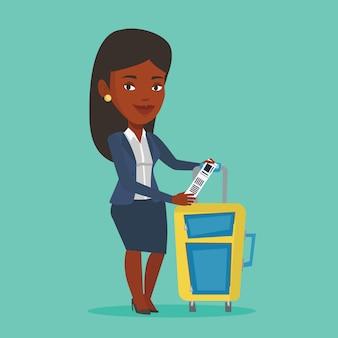 Donna di affari afroamericana che mostra l'etichetta dei bagagli