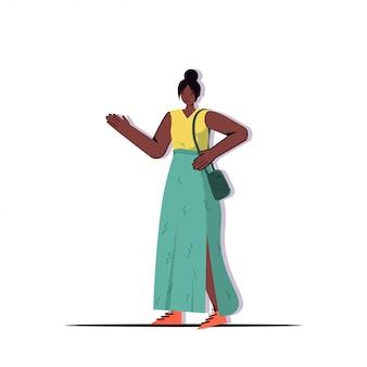 Donna di affari afroamericana in vestiti d'avanguardia casuali che tengono il personaggio dei cartoni animati femminile della borsa