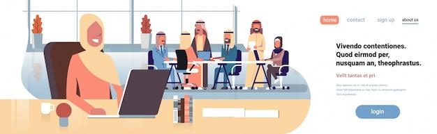 Donna di affari araba che usando l'insegna del posto di lavoro del computer portatile