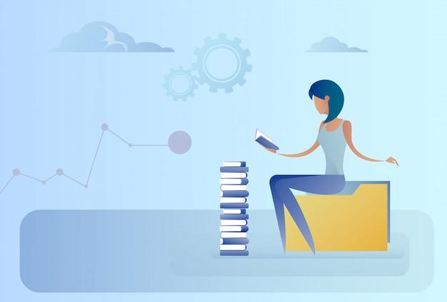 Donna di affari che si siede al concetto di istruzione della lettura della pila di libri