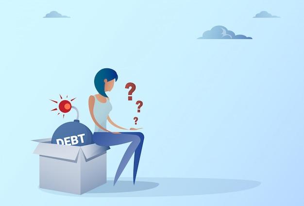 Donna di affari che si siede sul concetto di crisi di finanza di debito di credito della bomba