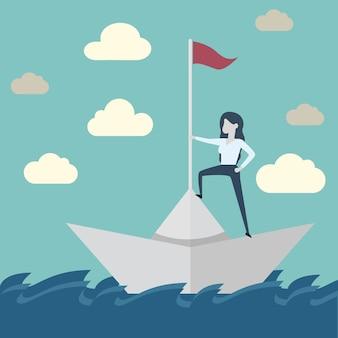 Donna di affari sulla barca di carta che naviga nel mare