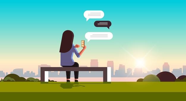 Donna di retrovisione che si siede sulla panchina utilizzando chat mobile app sulla comunicazione bolla di chat di rete sociale dello smartphone