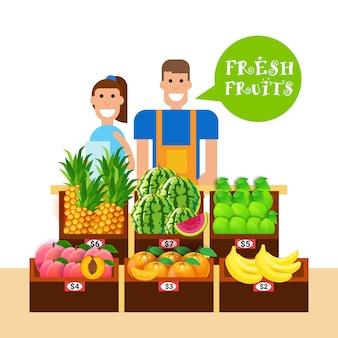 Donna ed uomo che vendono frutta fresca sul concetto sano naturale dei prodotti del mercato dell'alimento biologico