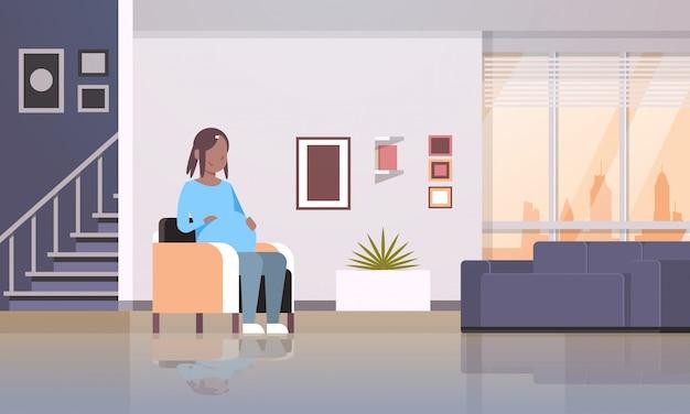 Donna felice che si siede nella poltrona poltrona tenendo il suo concetto di gravidanza e maternità urto moderno