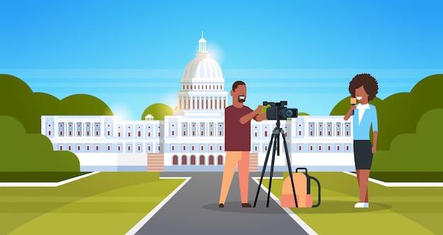 Donna giornalista con reporter uomo presentando operatore di notizie in diretta utilizzando la videocamera su treppiede registrazione corrispondente film rendendo concetto orizzontale bianco casa washington ds sfondo