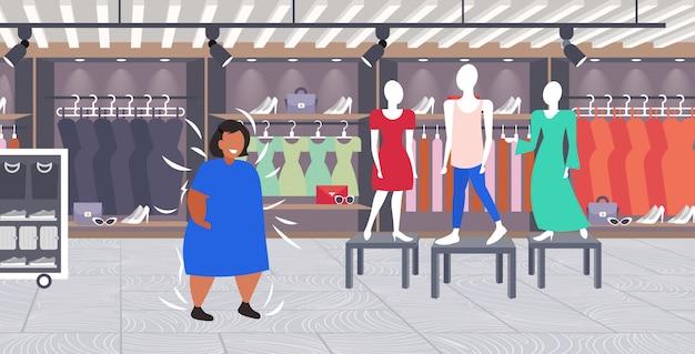 Donna grassa obesa che sceglie nuovo vestito nel negozio di moda su ragazza di dimensioni visitando abiti femminili mercato concetto di obesità centro commerciale interno boutique