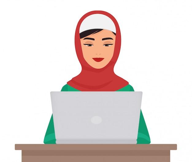 Donna graziosa di affari musulmani in abbigliamento tradizionale che lavora al computer portatile isolato