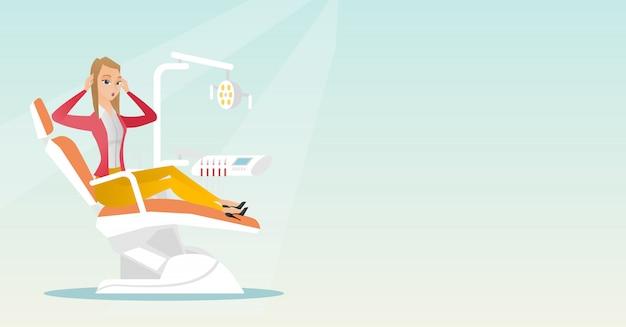 Donna impaurita che si siede nella sedia dentale.