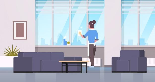 Donna in guanti e finestre di pulizia del grembiule con straccio detergente spray casalinga vista posteriore facendo lavori domestici concetto moderno salotto interno