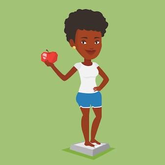 Donna in piedi sulla scala e tenendo in mano la mela.