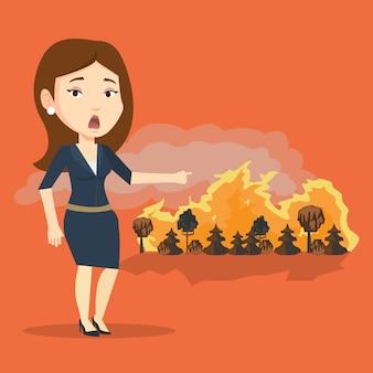 Donna in piedi sullo sfondo di un incendio.