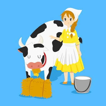 Donna lattaia e una mucca che mangia fieno