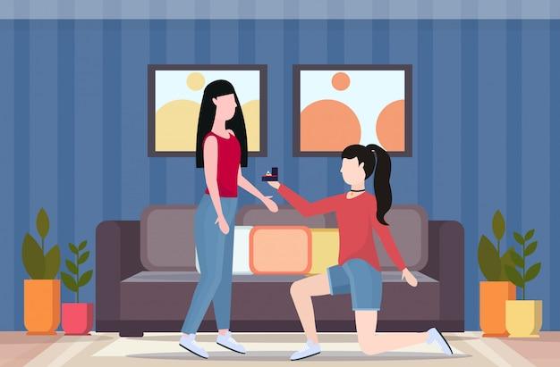 Donna lesbica in ginocchio tenendo l'anello di fidanzamento proponendo la fidanzata sposa la sua coppia donne omosessuali matrimonio offerta concetto moderno soggiorno interno a figura intera piano orizzontale
