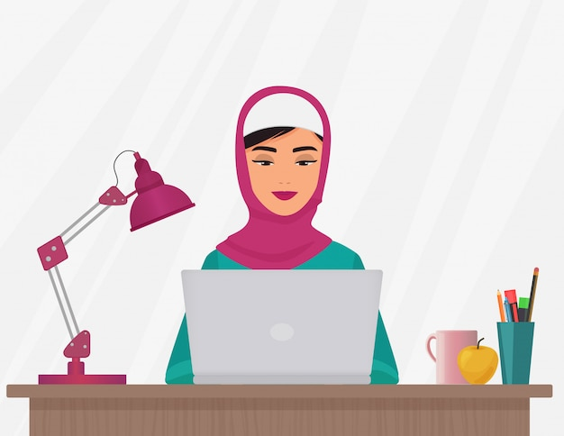 Donna musulmana che lavora al computer portatile