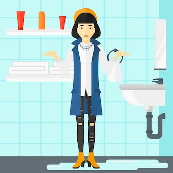 Donna nella disperazione che sta vicino al lavandino colante.